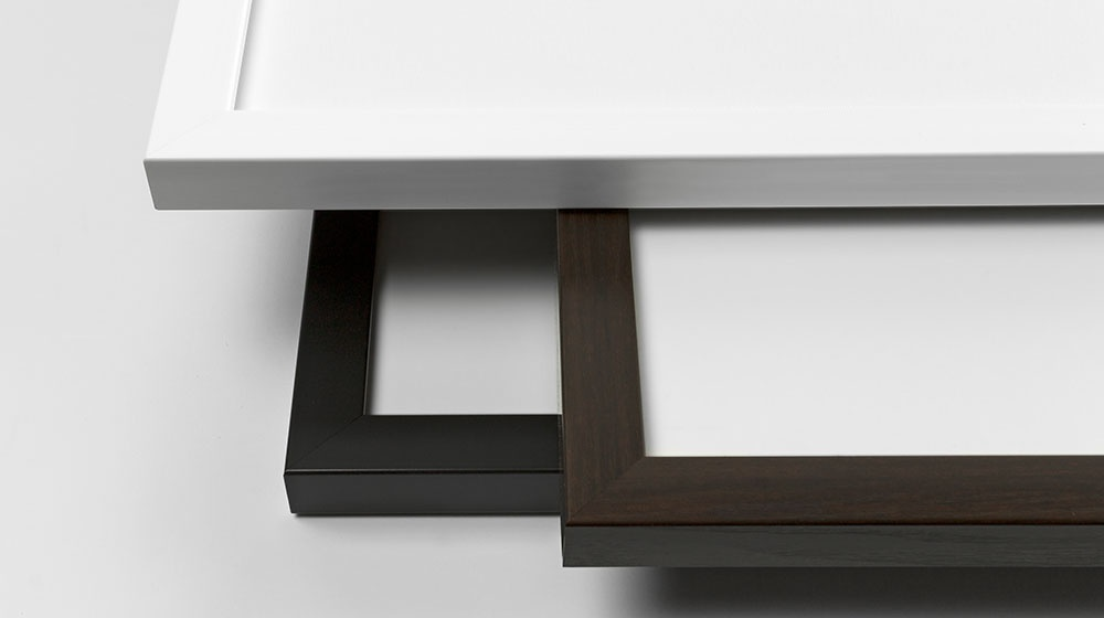 Three framed print finishes in black, white, and walnut