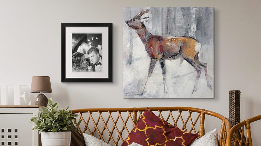 framed wedding photo next to a canvas print depicting a doe walking in snow