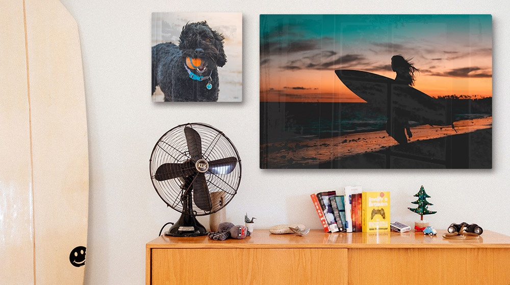 two acrylic photo prints of a surfer and dog over a sideboard