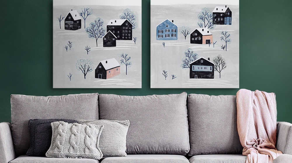 Two winter inspired art prints over a gray couch decorated with throw pillows and knit blanket