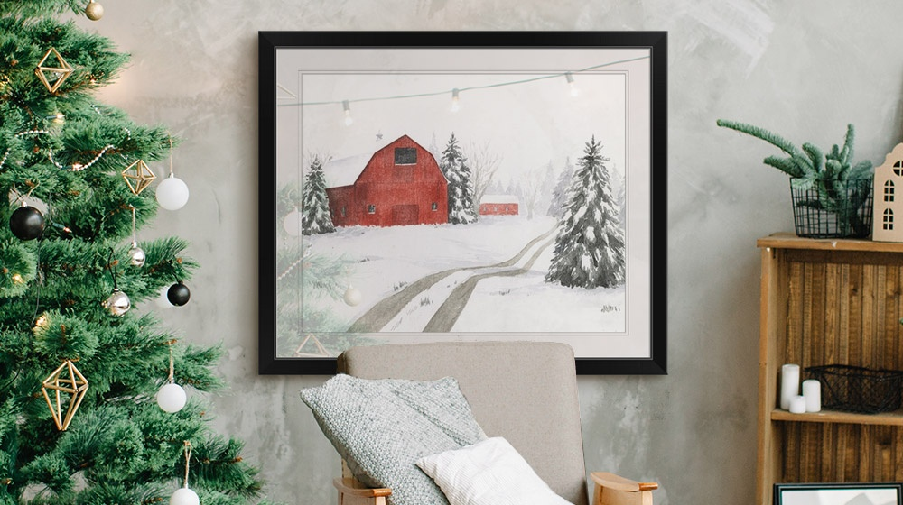 wintery barn framed print hanging on wall next to Christmas tree and décor