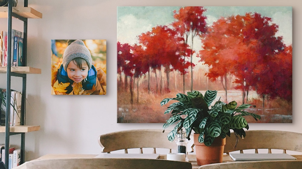 A dining room features fall landscape canvas wall art