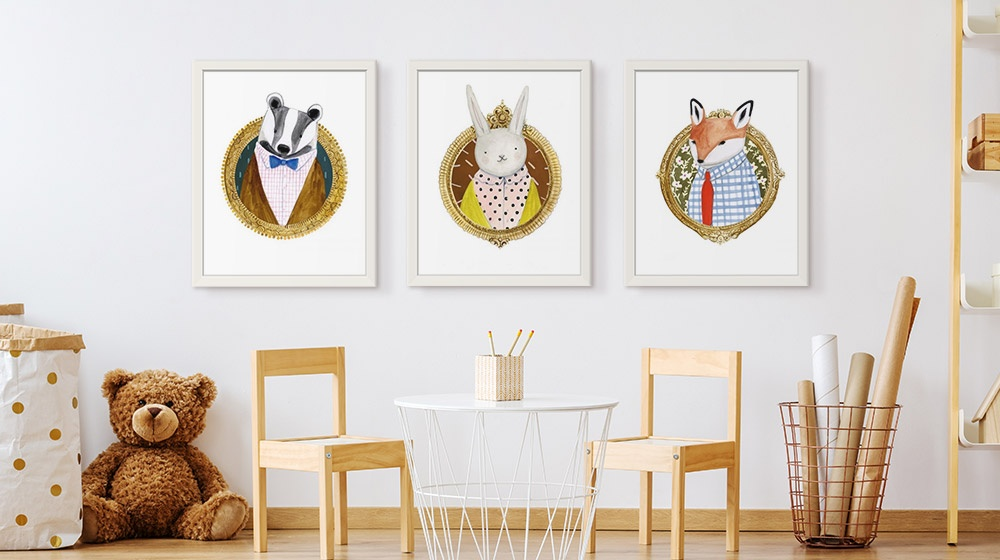 three white framed prints of woodland animals on wall in kids room