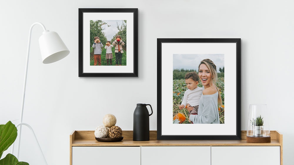 Two framed prints over a cabinet featuring a autumn family photos