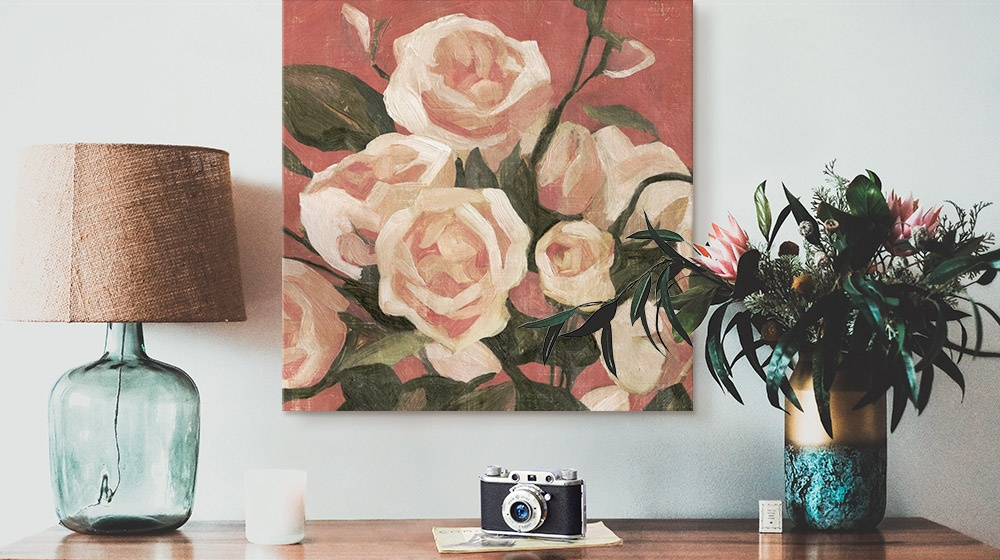 floral canvas hanging above table with lamp and camera and plant