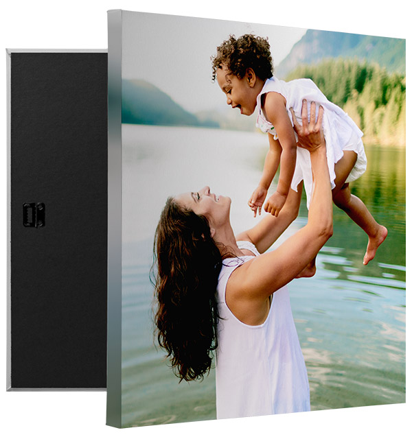 a mother lifting young girl in air while standing in front of a lake